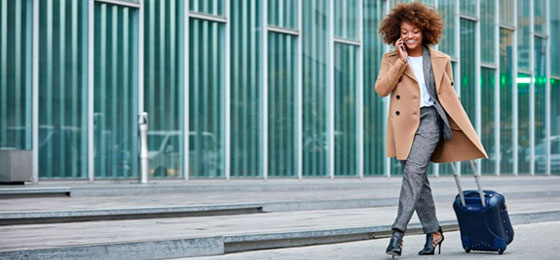 Business woman walking with a suitecase