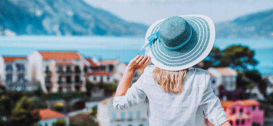 Woman holding her hat in place viewing scenary